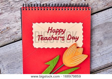 Red notebook on wooden surface. Greeting card for dear teacher.