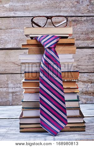 Glasses and tie. Books on wooden shelf. Men's business lifestyle.