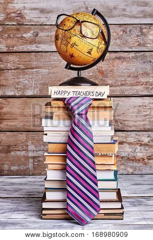 Glasses on globe and tie. Stack of books and card. Congratulate geography teacher.