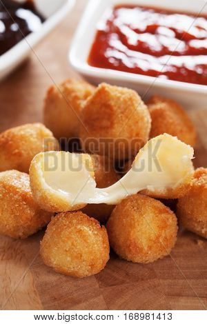 Breaded and fried mozzarella cheese balls with tomato sauce