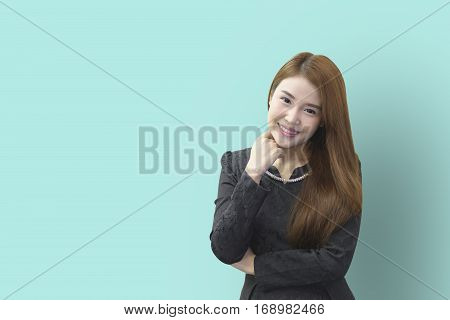 A smile face of pretty Asian business woman with the light green background.The young pretty office woman have happy with the light green wall