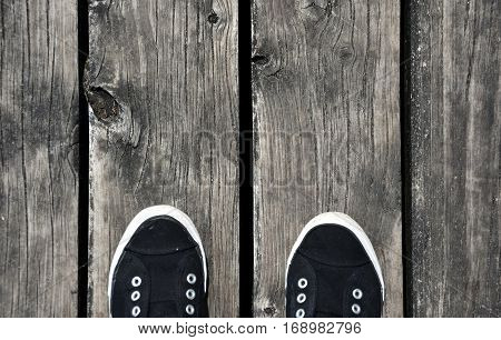 Black and white Shoes stand on old wooden pier floor. Wood pier abstract texture of a natural gray. View of old weathered deck wooden board.