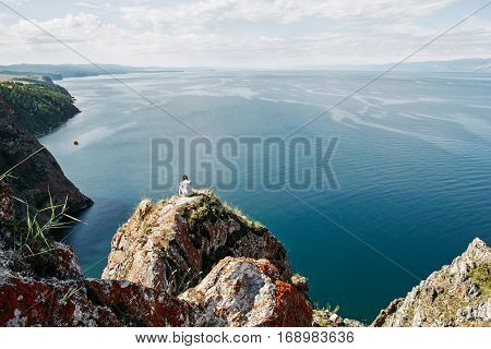 Brooding man sits on the edge of rock in front of the open water space, top view