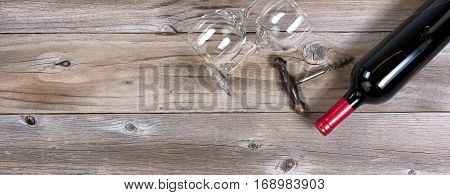 Flat view of a bottle of red wine antique corkscrew and drinking glasses on rustic wooden boards