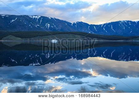 Landscape with beautiful reflections in water and white ship near the coast