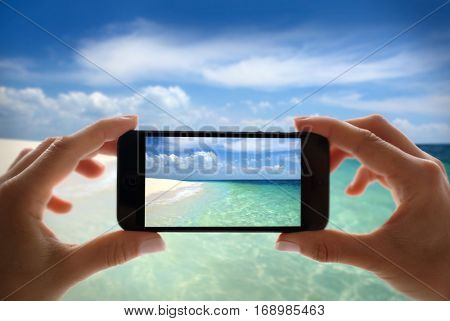 Woman using cell phone for taking sea landscape photo