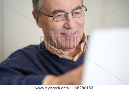 Senior man relaxing in sofa, websurfing on tablet