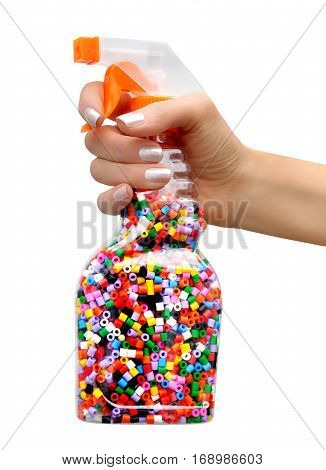 Sprayer with colorful plastic beads inside a woman's hand on white background