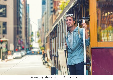 San Francisco hipster man taking public cable car transport for tourism travel. University student with bag morning commute in city street. Urban modern lifestyle.