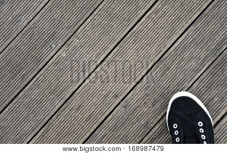 Black and white Shoes stand on old wooden pier floor. Wood pier abstract texture of a natural gray. View of old weathered deck wooden board. Diagonal wood background texture.