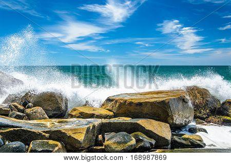 Sea Water Hitting Into Rocks On Coast And Splashing Water Drops.