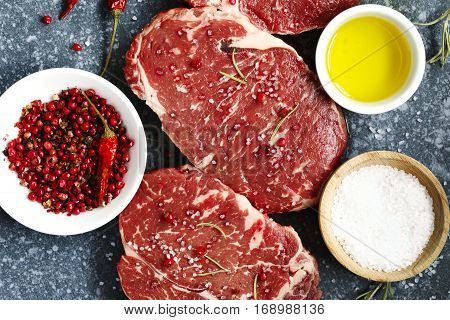 Raw fresh meat Ribeye Steak with rosemary pepper and sea salt on stone slate background