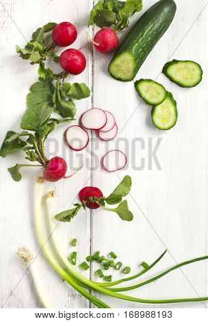 Spring vegetables on wooden background with copy space. Carrots radish cucumber and green onion - fresh harvest from the garden.