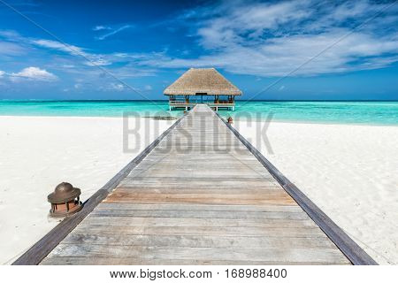 Wooden jetty leading to relaxation lodge. Maldives islands resort on Indian Ocean