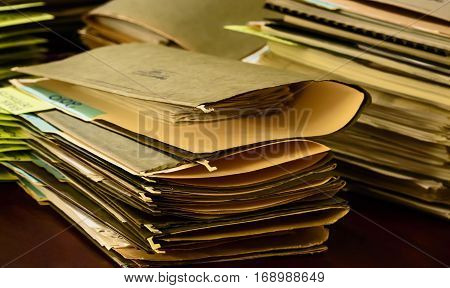 Tax preparation stack of files and paperwork bills and receipts in old vintage files on desk social share image or promotional photography poster