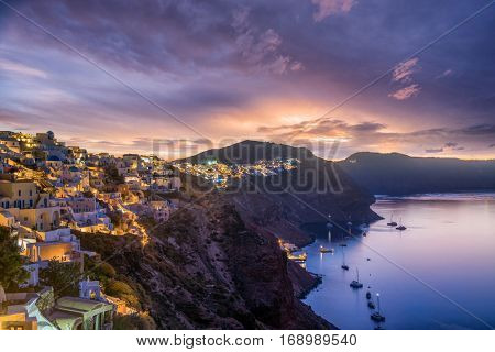 Picturesque view, Old Town of Oia or Ia on the island Santorini, white houses, windmills and church with blue domes at sunset, Greece