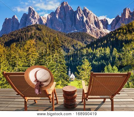 Two deck chairs on a wooden floor installed to relax and review the Alps. The concept of eco-tourism in Alpine meadows. Beautiful autumn day