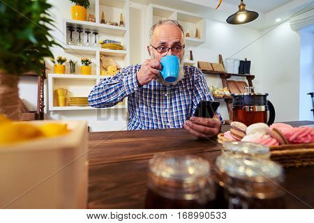 Side low angle of surprised face of mature man looking at the screen of the telephone. Man sitting at the table and reading news