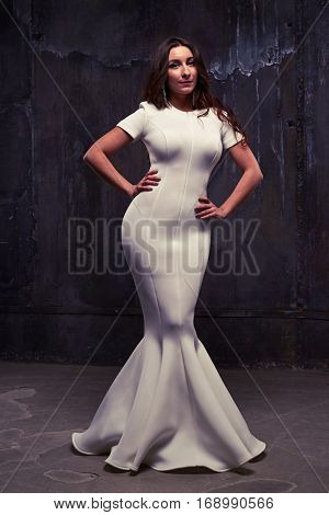 Low angle shot of a magnificent young woman in a white fishtail maxi dress over black worn background. Pretty longhaired brunette with hands on hips posing at the camera in studio