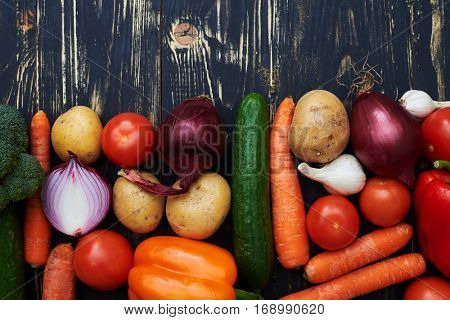 Close-up of well-arranged vegetables placed over wretched background. An assortment of organic vegetables for healthy diet over rustic wooden background