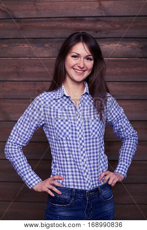 Studio portrait of pretty young lady. Wearing trendy clothes. Posing with hands on hips isolated over wooden background