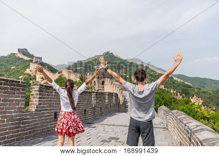 Happy winner couple cheering with arms up of success at Great Wall of China having fun during summer travel. Young people tourists at famous chinese tourist attraction.