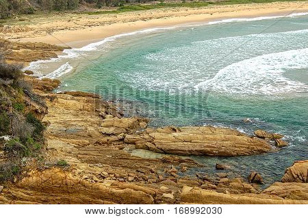 Gentle waves wash and erode the rocks in Nelson Beach on the Sapphire Coast of New South Wales, Australia