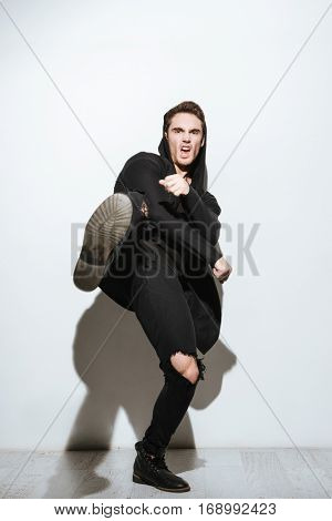Image of young screaming man dressed in black t-shirt and mantle standing over white background and posing.