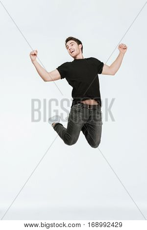 Picture of happy young man dressed in black t-shirt jumping over white background looking aside.