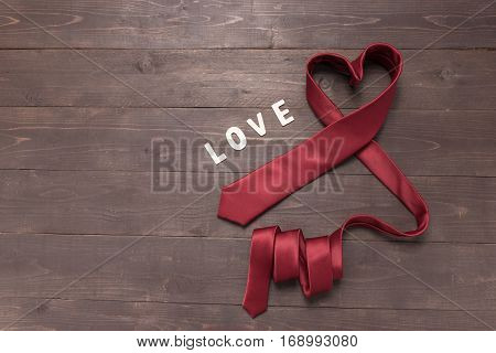 Red Heart Necktie Is On Wooden Background