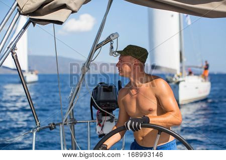 Man at the helm controls of a sailing boat during sea yacht race.