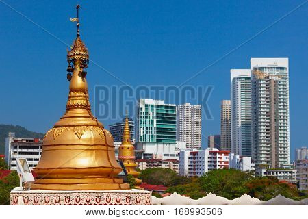 Golden buddhist stupa on modern city buildings background. Pagoda exterior of ancient Burmese buddhist temple Dhammikarama in Georgetown on Penang island. Asian arts culture. Travel in Malaysia.