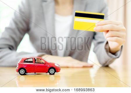 Real estate investment by credit card. Car on table.