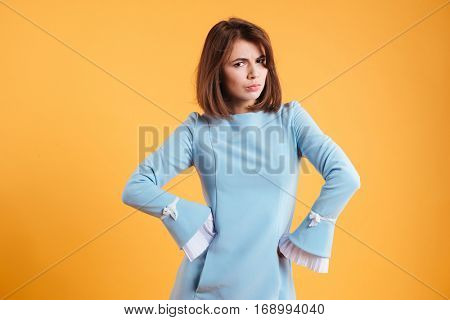 Frowning serious young woman standing with hands on waist over yellow background