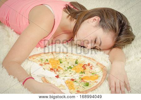 sad overeat girl lying with pizza pieces
