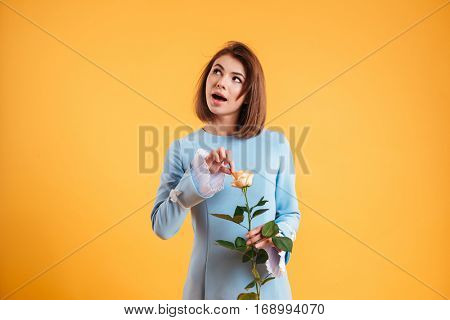 Thoughtful young woman holding pink rode and tearing petals over yellow background