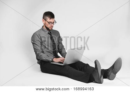 Handsome young programmer with laptop on light background