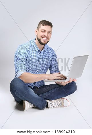 Handsome young programmer with laptop on color background