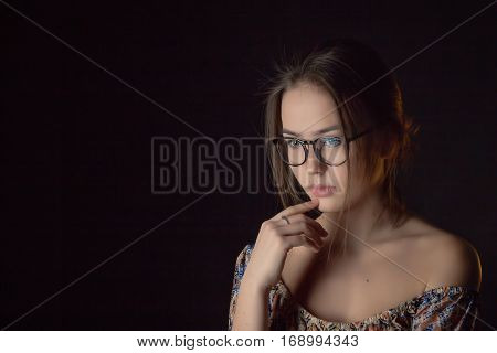 beautiful girl thinker on black background with copyspace