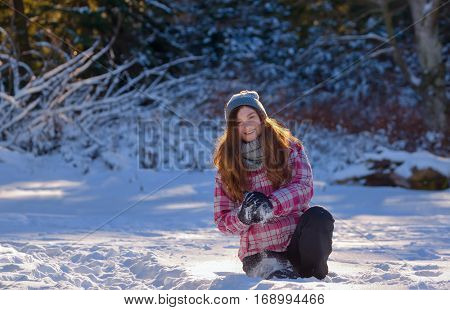 teen girl playing in snow throwing snowball at camera