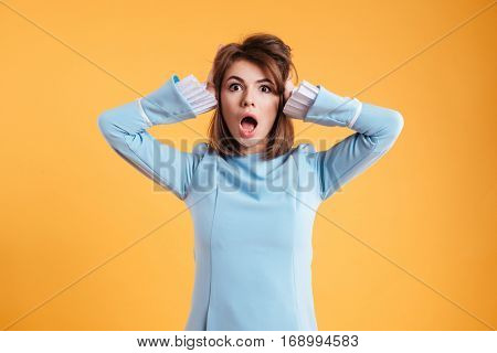 Shocked amazed young woman with hands on head standing and shouting over yellow background