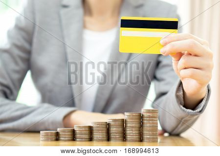 Businesswomen hand with credit card and many coins in column