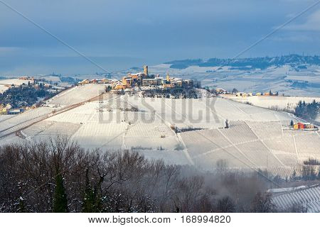 Small medieval town on snowy hill in winter in Piedmont, Northern Italy.