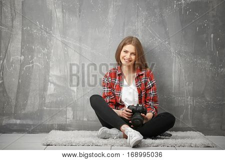 Beautiful young photographer sitting on floor near grunge wall