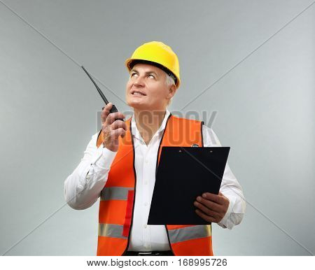 Senior engineer with portable radio transmitter and clipboard on light background