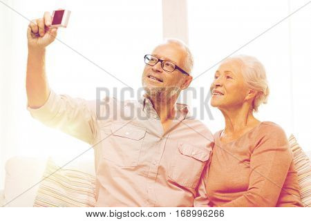 family, technology, age and people concept - happy senior couple taking selfie with camera at home