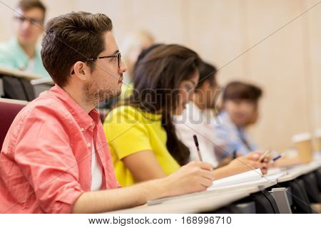 education, high school, university, learning and people concept - group of international students with notebooks writing in lecture hall and talking