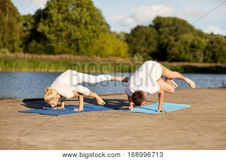 fitness, sport, yoga, people and healthy lifestyle concept - couple making side crane pose on mat on river or lake berth