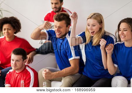 people, leisure, rivalry and sport concept - happy friends or football fans watching soccer game or match and celebrating victory at home