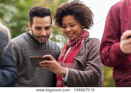 people, friendship, communication, technology and international concept - group of happy friends with smartphone outdoors
